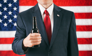 Preppy Man with a beer in front of the Flag